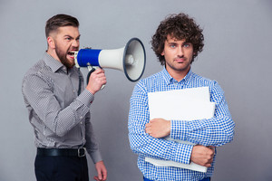 Businessman screaming via megaphone to another man