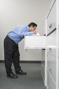 Businessman searching in filecabinet in office