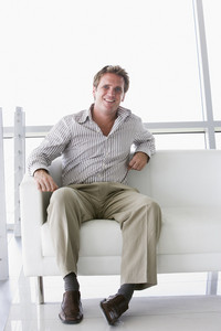Businessman sitting in office lobby smiling