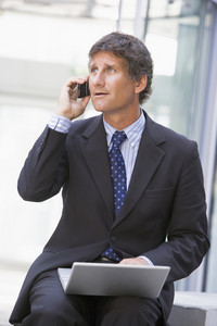 Businessman sitting in office lobby with laptop using cellular phone