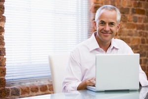 Businessman sitting in office on laptop smiling