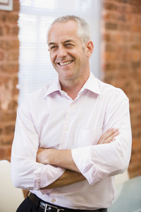 Businessman sitting in office space smiling