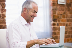 Businessman sitting in office typing on laptop smiling