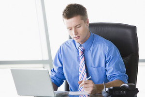Businessman sitting in office with laptop writing note