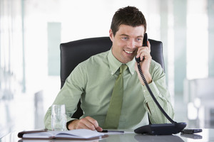 Businessman sitting in office with personal organizer on telephone