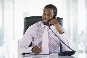 Businessman sitting in office with personal organizer open on telephone