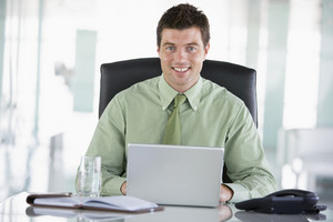 Businessman sitting in office with personal organizer using laptop smiling