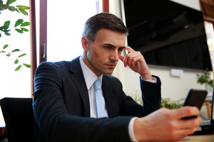 Businessman sitting on his workplace and using smartphone in office