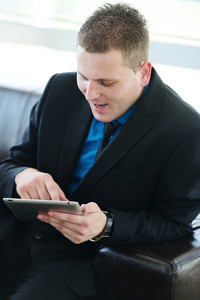 Businessman sitting on leather sofa using tablet