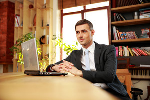 Businessman sitting with laptop at office