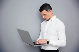 Businessman standing and using laptop over gray background