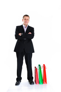 Businessman standing beside shopping bags with folded arms
