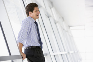 Businessman standing in corridor laughing