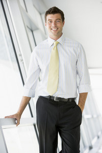 Businessman standing in corridor smiling
