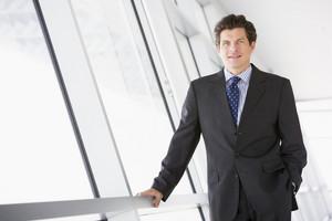 Businessman standing in corridor smiling