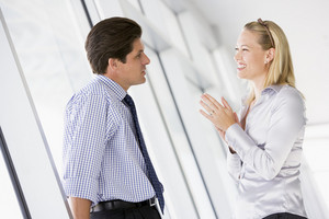 Businessman standing in corridor talking to smiling businesswoman