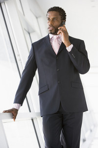 Businessman standing in corridor using cellular phone