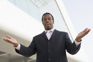 Businessman standing outdoors by building with hands out smiling