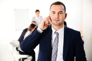 Businessman talking on the smartphone in front of business meeting
