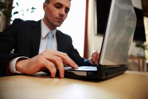 Businessman using laptop at office. Focus on laptop.