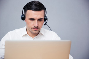 Businessman using laptop in headphones