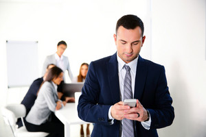 Businessman using smartphone in front of business meeting