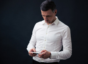 Businessman using smartphone over black background