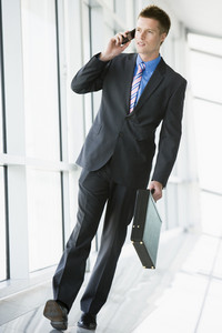 Businessman walking in corridor using cellular phone