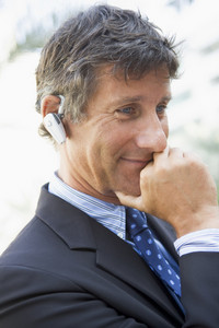 Businessman wearing headset outdoors