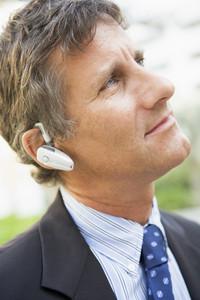 Businessman wearing headset outdoors