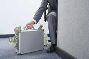 Businessman with briefcase of money