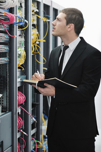 Businessman withnotebook in network server room