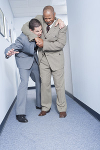 Businessmen fighting in office