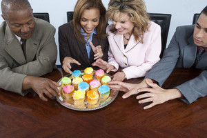 Businesspeople eating cupcakes in office