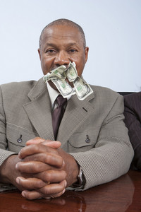 Businessperson with cash in mouth