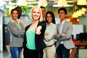 Businesswoman giving thumb up to camera in front of colleagues