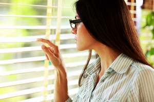 Businesswoman in glasses looking in window at office