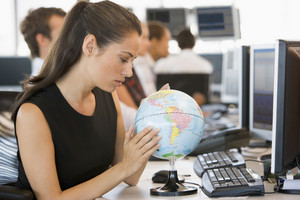 Businesswoman in office space with desk globe
