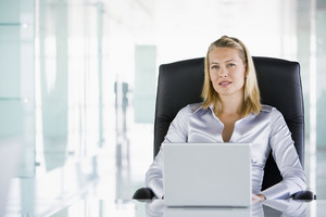 Businesswoman in office with a laptop
