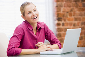 Businesswoman in office with laptop laughing