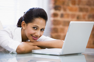 Businesswoman in office with laptop smiling