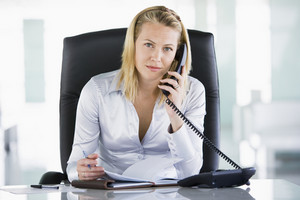 Businesswoman in office with personal organizer open on telephone