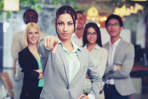 Businesswoman pointing at camera in front of colleagues
