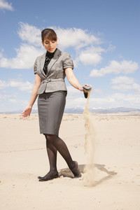 Businesswoman pouring sand out of shoe