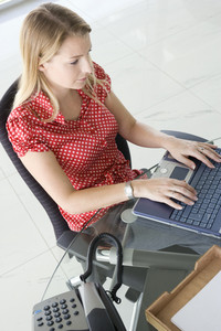 Businesswoman sitting in office typing on laptop