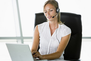 Businesswoman sitting in office wearing headset using laptop