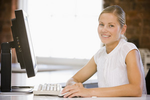 Businesswoman sitting in office with computer smiling