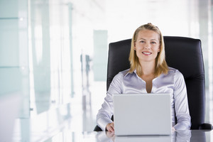 Businesswoman sitting in office with laptop smiling