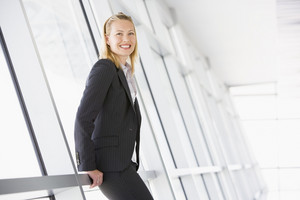 Businesswoman standing in corridor smiling