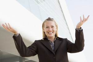 Businesswoman standing outdoors by building smiling with hands out
